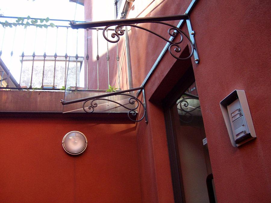 divisori in ferro e vetro : Tettoia in ferro battuto e vetro - protezione porta dingresso